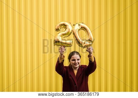 Young Beautiful Sad Girl In Burgundy Coat And Mustard Sweater Holds In Her Hands The Helium Balloons