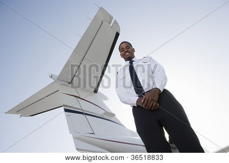 Low angle view of young pilot standing with airplane tail in background