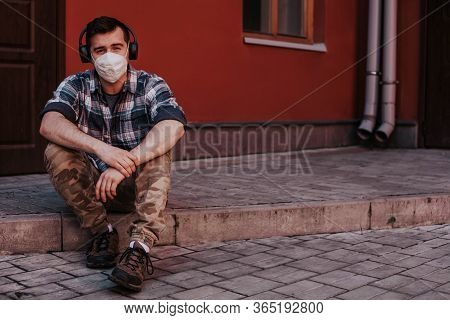 A Guy In A Mask And Headphones Sits On The Doorstep Home And Listens To Music