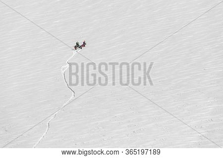 Group Of Hikers And Skiers On A Huge Giant Snowfield Up In The Mountains With A Visible Trail Of The