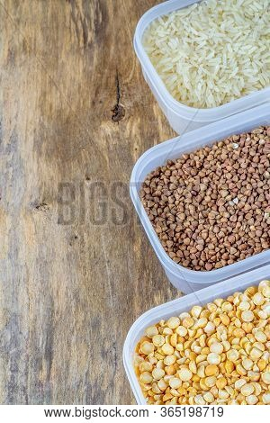 Raw Rice, Buckwheat And Dry Peas In Plastic Containers On Wooden Background