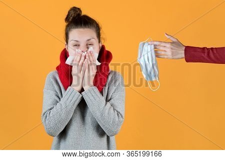 A Girl With Symptoms Of The Virus And A Cold Is Offered To Wear A Mask. A Hand Holds Out A Medical M