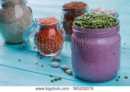 Overfilled Split Peas In A Glass Can. Close Up Grains And Cereals On Glass Containers On Blue Wooden