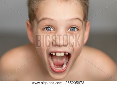 A Cute Boy Screams With Joy. A Freestanding Young Man On A Gray Background With Jagged White Teeth I