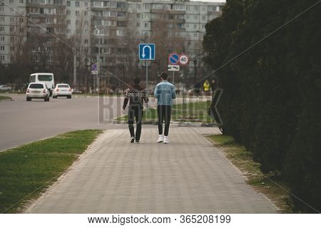 Two Friends Are Walking Along A Road In The City