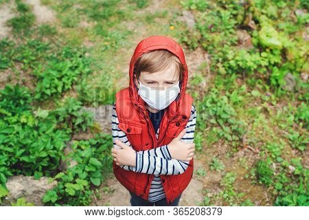 Sad Boy Wearing Face Mask Outdoors. Worried Child On A Walk In Nature Durind Pandemic. Coronavirus Q