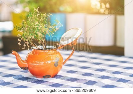Old Teapot Repurposed As A Vase For Bouquet On Table, Warm Light Of Sunset On Background.cozy Design