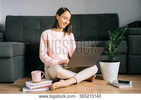 Happy Young Woman Sitting On The Floor Near Couch And Using Laptop, Calling Her Friends Or Family By