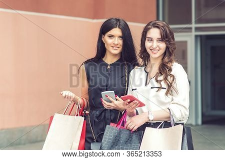 Two Fashionable Women Are Looking At Camera With Smartphones And Shopping Bags At Mall. Two Girls Lo