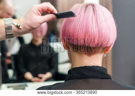 The Hairdresser Is Using Comb For Female Pink Hair At Beauty Salon. Male Hand Is Combing Woman Short