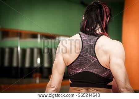 Unrecognizable Woman Athlete Doing Exercises With Weights And Dumbbells In The Gym. Engaging Trapezi