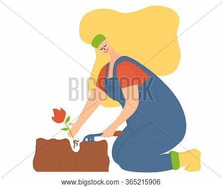 Woman With Garden Hoe In Hand Plants A Flower. Blonde Hair, Blue Jumpsuit,