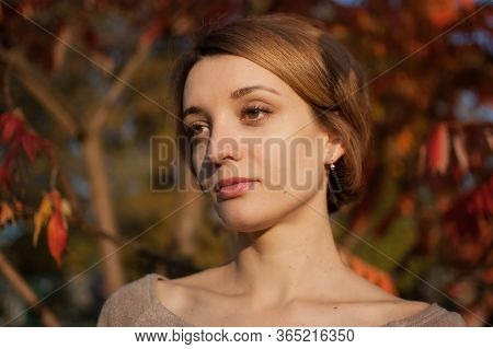 Outdoors Portrait Of Young Girl With Short Blond Hair During Sunny Weather In Autumn On Red And Oran