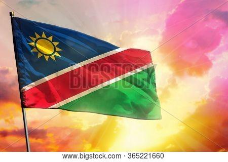 Fluttering Namibia Flag On Beautiful Colorful Sunset Or Sunrise Background. Namibia Success And Happ