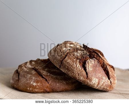 Two Round Loaves Of Rye Bread On The Table. One Loaf Is On Top Of The Other. Front View.