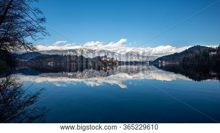 Bled Lake In Slovenia With Blue Sky And Clouds, Apls Mountains Behind. Traveling At Slovenia, Landsc