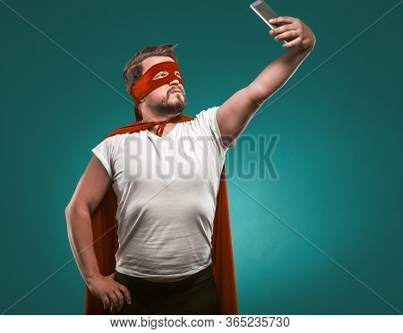Super Hero Man Takes Selfie By Mobile Phones. Man In A Super Hero Costume In A Red Mask And Cloak Is