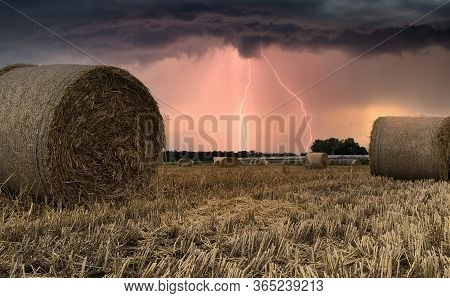Summer Thunderstorm And Lightning And Looms Over Harvested Hay Field With Hay Bales In The Kempen Ar