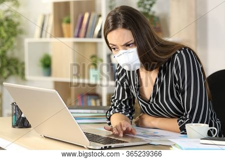 Suspicious Entrepreneur Woman Reading Fake News On Laptop Sitting On A Desk At Homeoffice