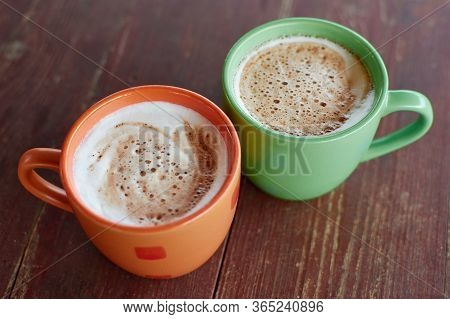 Two Cups Of Fragrant Cappuccino On A Wooden Roofing Paper. Airy Milk Foam Of A Hot Drink. Coffee Dri
