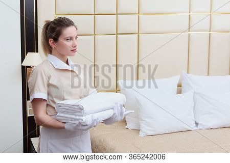 The Maid Tidies The Room Of An Expensive Hotel. The Concept Of The Hotel Business.