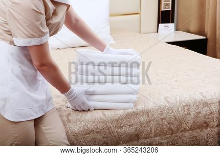 The Maid Changes Towels In The Hotel Room.unrecognizable Photo. The Concept Of The Hotel Business.