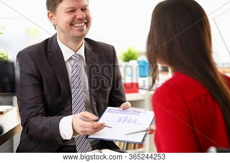 Man In Suit Holds Out Signature Document To Woman. Boss Laughs And Shows Statistical Report To Emplo