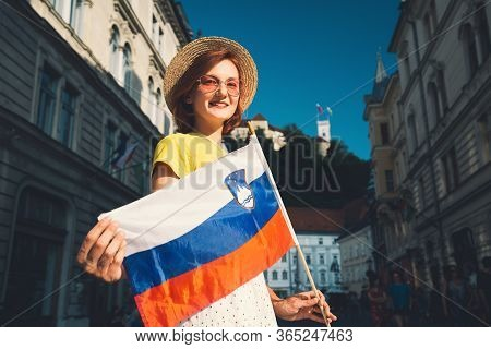 Young Smiling Girl In Sunglasses With Slovenian Flag On Central Square Of Ljubljana. Woman Tourist H