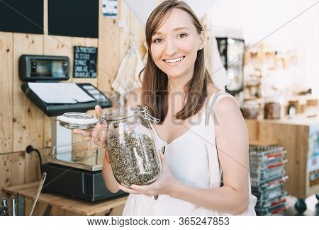 Girl Holds Glass Jar With Hemp Seeds. Woman With Cotton Reusable Bag Chooses And Buys Products In Ze