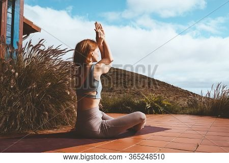 Woman Meditating And Doing Yoga On Terrace Of Home.