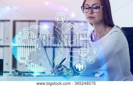 European Businesswoman Making Notes At Blurry Table With Laptop And Double Exposure Of Futuristic On