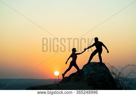 Man And Woman Hikers Helping Each Other To Climb A Big Stone At Sunset In Mountains. Couple Climbing