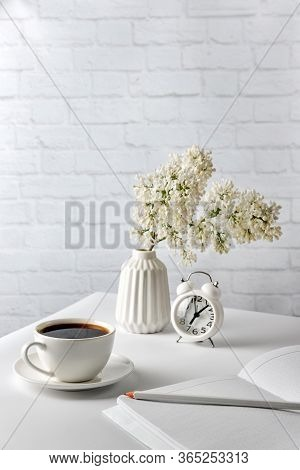 Cup Of Coffee, Notebook, Pencil, Alarm Clock And A Vase With Lilac Flowers On A White Table On A Bac