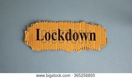 Word Lockdown On The Piece Of Cardboard On Blue Fon.