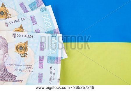 Ukrainian Hryvnia, Several Banknotes Of 1000 Hryvnia Against The Background Of The Flag Of Ukraine.