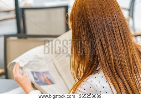 Redhead Woman Read Newspaper In The Cafe. Shoot From Behind Young Girl Read News. Sunny Day.