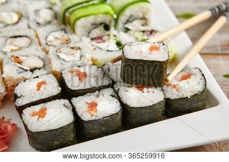 Roll set in ceramic white plate with chopsticks. Delicious sushi, asian cuisine, healthy nutrition, traditional japanese food with rice and fish close up. Served seafood, restaurant meal