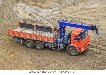 Top View Of A Flatbed Truck With A Blue Crane Arm Parked On A Sand Construction Site