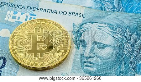 Electronic Bitcoin Coins, With A Hundred Dollar Bill In The Background. Devaluation Of The Brazilian
