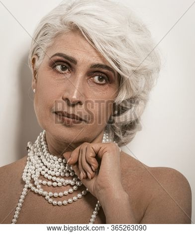 Stylish Senior Nude Woman With Well-groomed Skin On White Background. Mature Woman With Pearl Beads