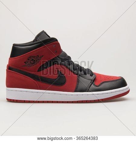 Vienna, Austria - June 14, 2018: Nike Air Jordan 1 Mid Black, Red And White Sneaker On White Backgro