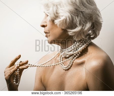Naked Mature Woman On White. Profile View Of A Mature Woman Showing Pearl Beads On Her Neck And Bare