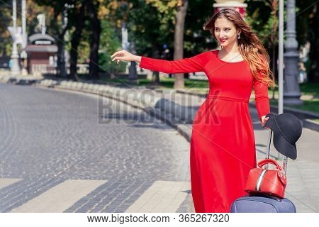 Smiling Tourist Girl In Red Dress With Valise Catches A Taxi On Street Of City. Beautiful Tourist Wo