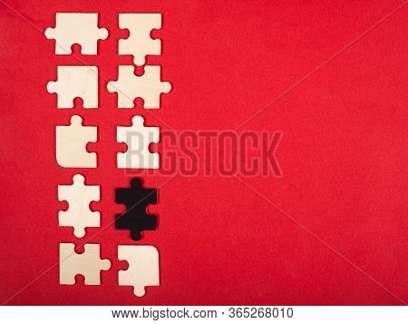 Wooden White And Black Puzzles On A Red Background Close-up Top View. Outcast Antisocial Leader Diff