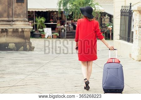 Back View Of Female In Black Hat Pulls The Suitcase On The City Street. Travel Woman Walking And Pul