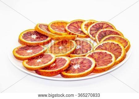 Sicilian Sliced orange On A White Plate On A White Background. Sliced Ripe Sicilian Oranges Agains
