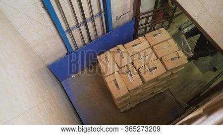 Crates Of Fish Rise On The Elevator. Boxes Rise On The Elevator. Fish Factory, Unloading Fish.