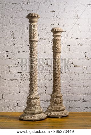 Two White Vintage Wooden Candlesticks On A Background Of Wooden Floor And White Painted Brick Wall