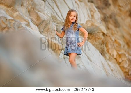 Brave Little Girl Standing On A Rock At Sunset By The Sea. Tourism And Travel With Children. New Exp