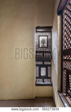 Corner Of Two Interleaved Grunge Wooden Ornate Windows - Mashrabiya - In Stone Wall In Abandoned Bui